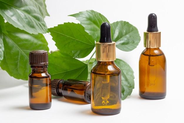 Стеклянные косметические флаконы с капельницей стоят рядом с зелеными листьями на белом фоне. концепция органической косметики, натуральное эфирное масло и сливки.