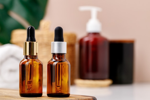 Glass cosmetic oil bottles with pipette in bathroom close up