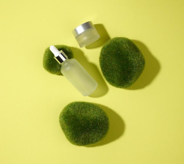 녹색-노란색 배경에 이끼 조각이 있는 피펫이 있는 유리 화장품 흰색 병. 화장품 spa 브랜딩 모형, 평면도