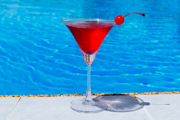Glass of cosmopolitan cocktail decorated with cherry on the edge of the infinity pool in the hotel