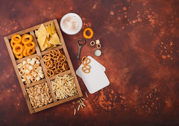 Glass of craft lager beer and opener with box of snacks on brown kitchen table. pretzel,salty potato sticks, peanuts, onion rings with nachos in vintage box with openers and beer mats.