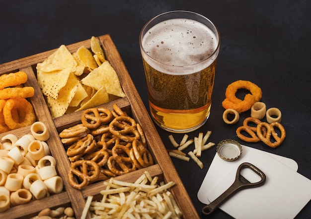 Glass of craft lager beer and opener with box of snacks on dark background. pretzel,salty potato sticks, peanuts, onion rings with nachos in vintage box with openers and beer mats. top view