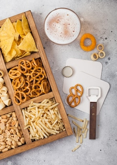Glass of craft lager beer and opener with box of snacks on light kitchen table. pretzel,salty potato sticks, peanuts, onion rings with nachos in vintage box with openers and beer mats.