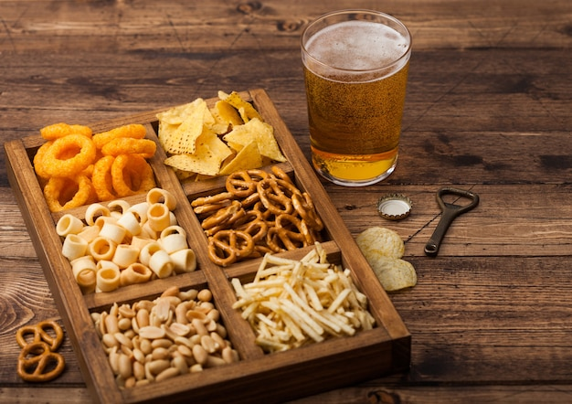 Glass of craft lager beer and opener with box of snacks on wood background. pretzel,salty potato sticks, peanuts, onion rings with nachos in vintage box with openers and beer mats.