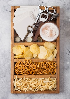 Glass of craft lager beer in vintage box of snacks openers and beer mats on light kitchen table table. pretzel and crisps and salty potato.