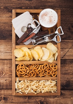 Glass of craft lager beer in vintage box of snacks openers and beer mats on wood background. pretzel and crisps and salty potato.