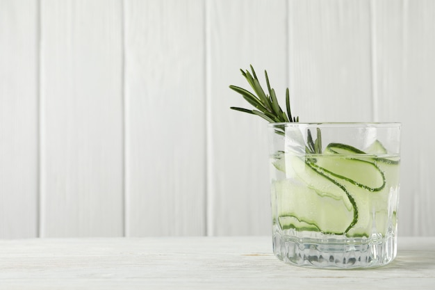 Glass of cucumber water on wooden table