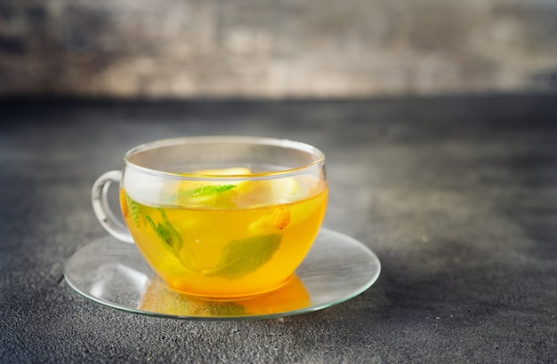 Glass cup of apple tea on dark grey surface