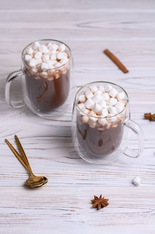 Glass cup of brown cocoa with marshmeloy, on white wooden background.