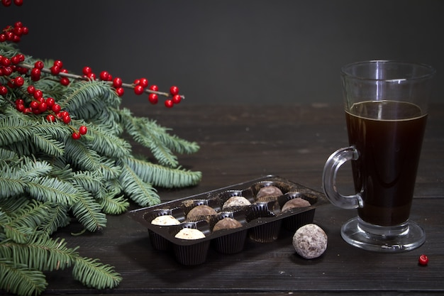 Glass cup of coffee, chocolate candies and christmas tree branches and red berries