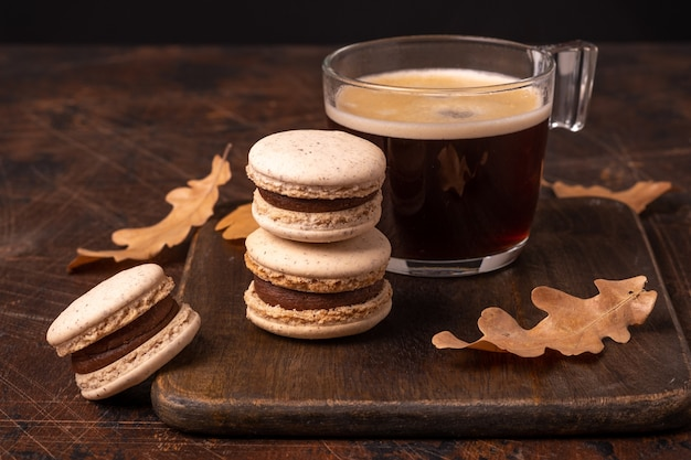Glass cup of coffee and chocolate macarons on wooden background. cozy autumn composition - image