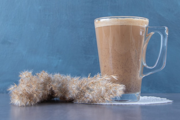 Glass cup of coffee latte on a coaster next to pampas grass , on the blue background. high quality photo