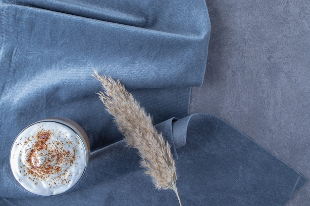 Glass cup of coffee latte on piece of fabric next to pampas grass, on the blue table.
