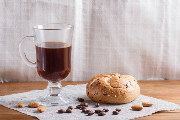 Glass cup of coffee with bun on a wooden background and linen textile.