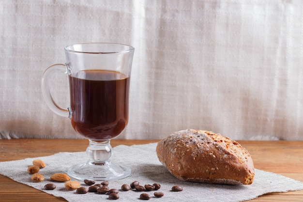 Glass cup of coffee with bun on a wooden table and linen textile.