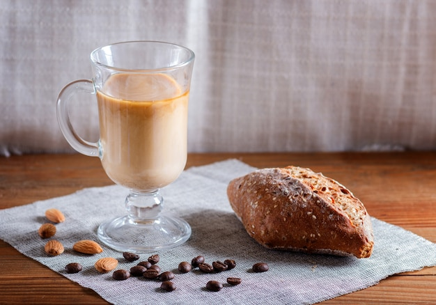Glass cup of coffee with cream  and bun on a wooden  table and linen textile.