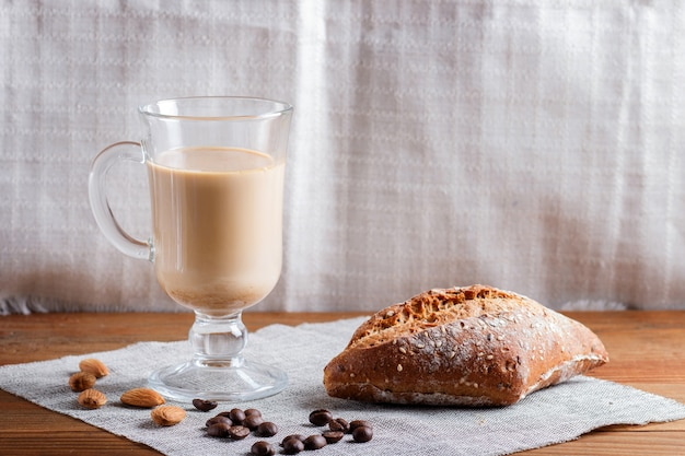 Glass cup of coffee with cream and bun