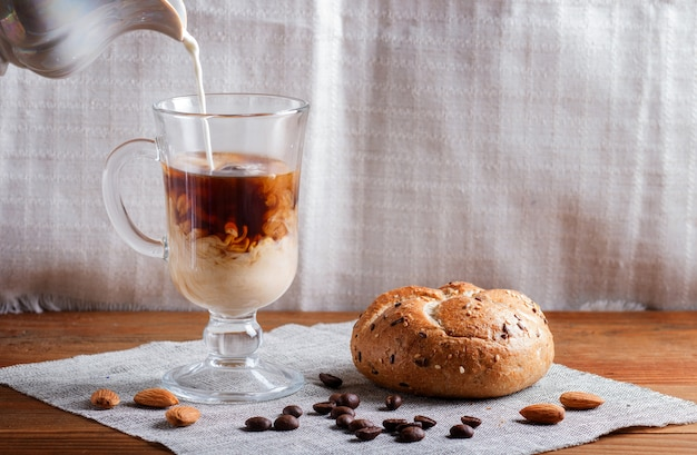 Glass cup of coffee with cream poured over and bun on a wooden  background and linen textile
