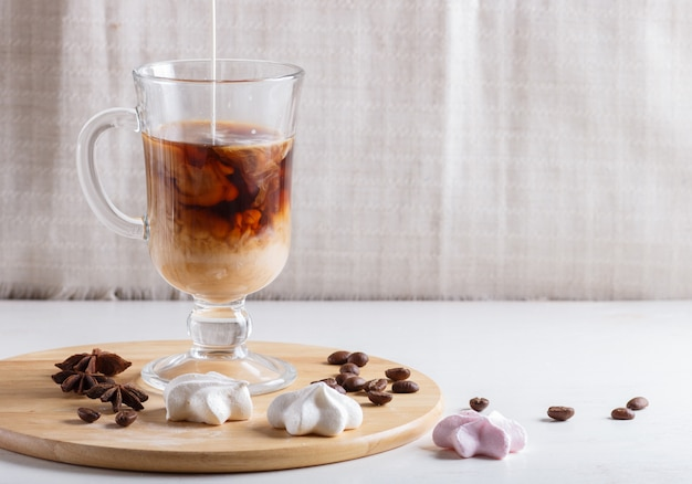 Glass cup of coffee with cream poured over and meringues on a wooden board on a white table.