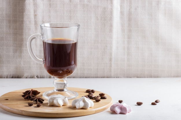 Glass cup of coffee with meringues on a wooden board on a white background.