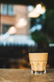 Tazza di caffè di vetro sullo scrittorio di legno con il contesto di caf� di defocus