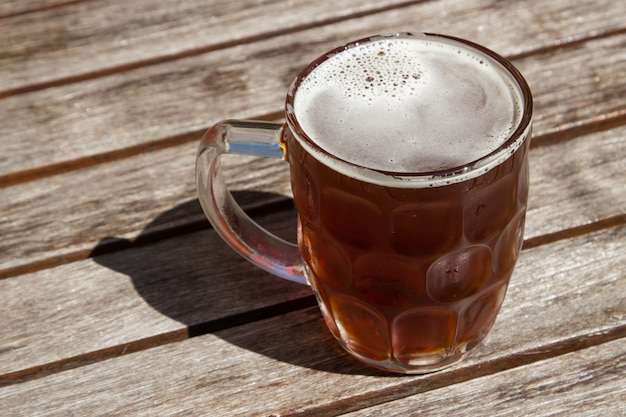 Glass cup of cold beer on a wooden surface on a hot sunny day