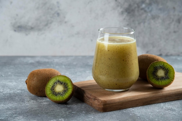 A glass cup of delicious kiwi juice on wooden board.