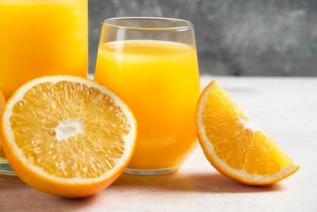 Una tazza di vetro di succo fresco con arancia a fette.