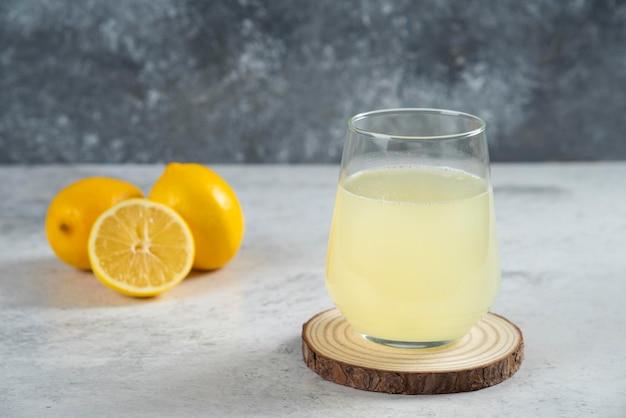 Una tazza di vetro di succo di limone fresco su una tavola di legno.