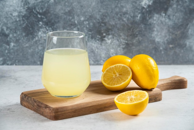 A glass cup of fresh lemon juice on a wooden board.