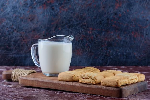 Una tazza di vetro di latte fresco con biscotti appena sfornati ripieni di frutta