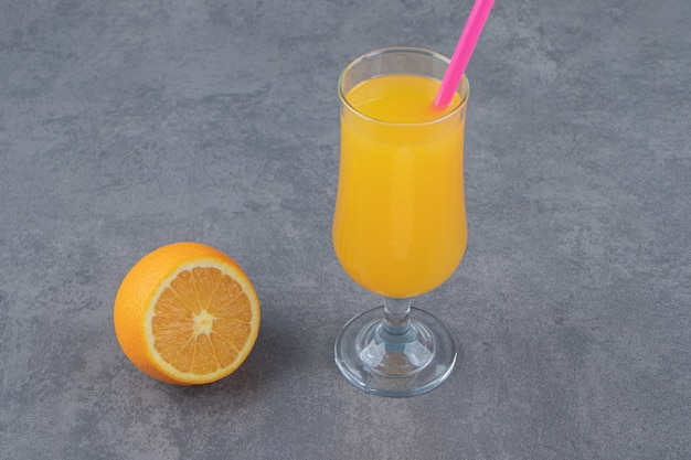 A glass cup of fresh orange juice with a slice of orange and straw
