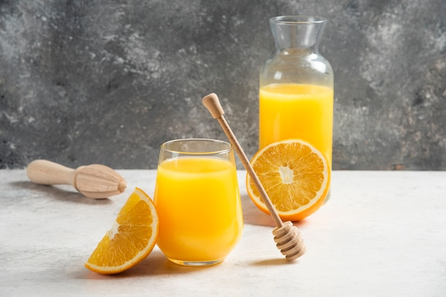 A glass cup of fresh orange juice with a wooden dipper.