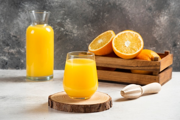 A glass cup of fresh orange juice on wooden board.