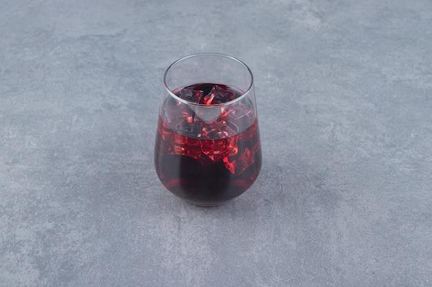 Una tazza di vetro di succo di melograno fresco con cubetti di ghiaccio. foto di alta qualità