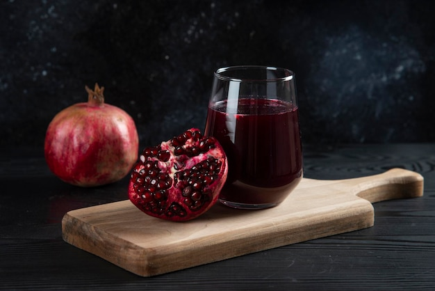 A glass cup of fresh pomegranate juice on wooden board.