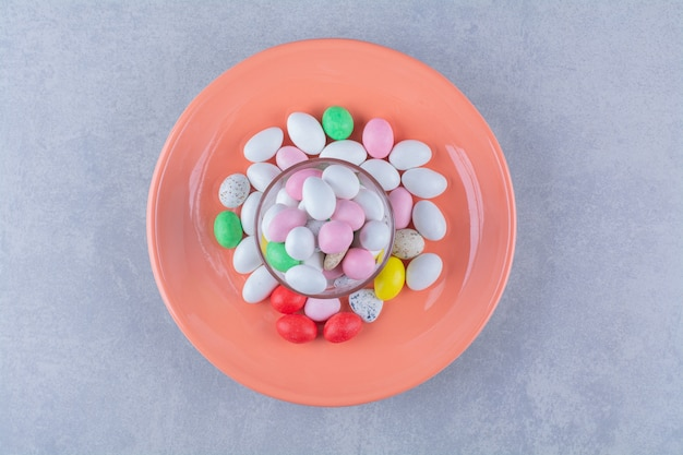 Una tazza di vetro piena di caramelle di fagioli colorate su una superficie grigia. foto di alta qualità