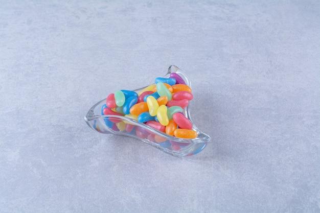 Una tazza di vetro piena di caramelle colorate di fagioli