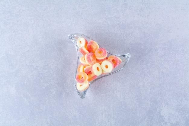 Una tazza di vetro piena di caramelle di gelatina di frutta colorate. foto di alta qualità