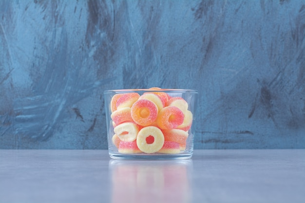 Una tazza di vetro piena di marmellate zuccherate di frutta colorata.