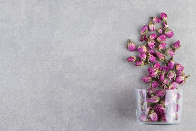 A glass cup full of dried rose flower buds placed on stone background.