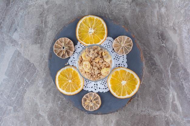 Una tazza di vetro piena di fiocchi di mais sani con fette di frutta secca d'arancia.