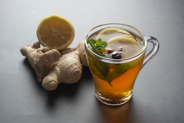 Glass cup of ginger tea with lemons and mint leaves on dark surface,