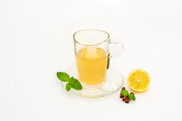 Glass cup of green tea with lemon and mint close up on the white surface
