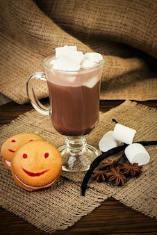 Glass cup of hot cocoa with marshmallows and cookies