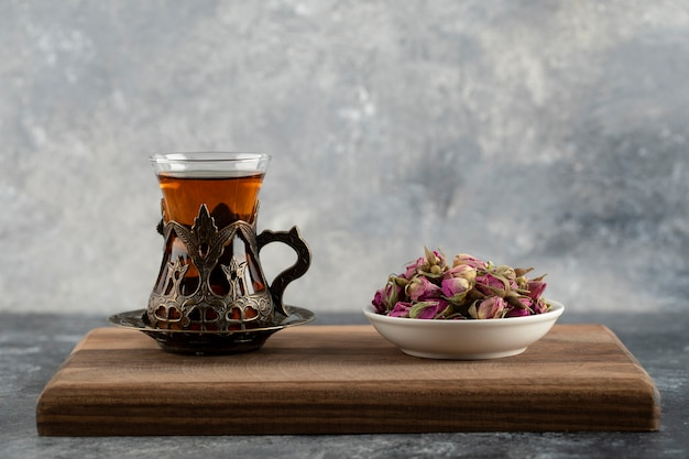 A glass cup of hot tea with dried roses on a wooden cutting board .