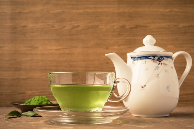 Glass cup of hot tea with green tea powder and teapot on the table.