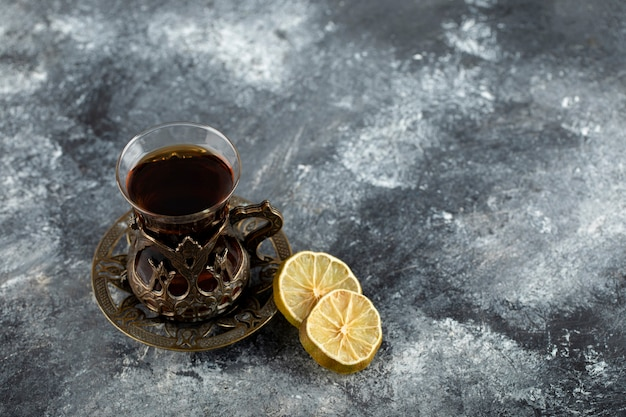 A glass cup of hot tea with slices of lemon .