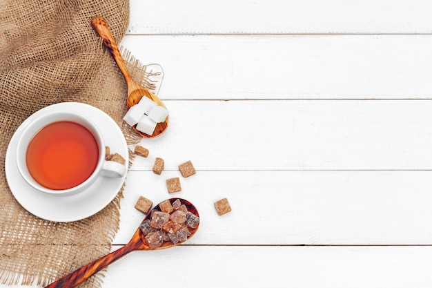 Glass cup of hot tea with sugar on the table background