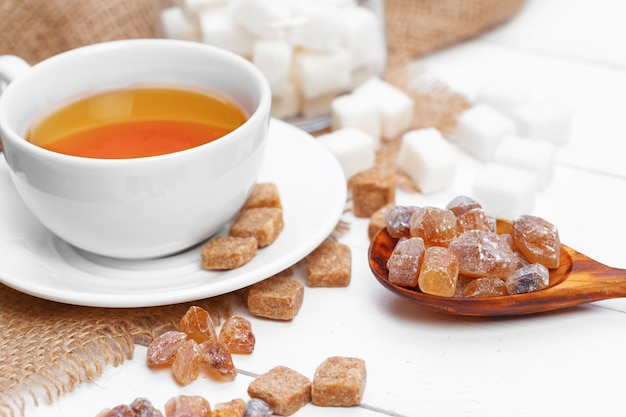 Glass cup of hot tea with sugar on the table